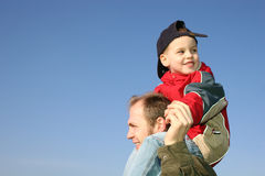 Son on father shoulders. Against blue sky royalty free stock photos