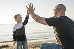 Son on father shoulders at the beach having fun  sunset together. A Son on father shoulders at the beach having fun at sunset together Stock Photography
