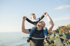 Son on father shoulders at the beach having fun  sunset together. A Son on father shoulders at the beach having fun at sunset together Stock Photos