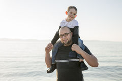 Son on father shoulders at the beach having fun  sunset together. A Son on father shoulders at the beach having fun at sunset together Royalty Free Stock Photos