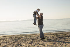 Son on father shoulders at the beach having fun  sunset together Royalty Free Stock Photography