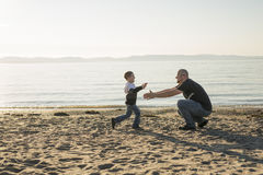 Son on father shoulders at the beach having fun  sunset together Stock Photos
