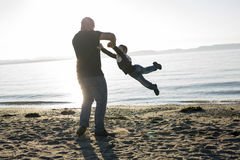 Son on father shoulders at the beach having fun  sunset together Royalty Free Stock Image