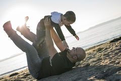 Son on father shoulders at the beach having fun  sunset together. A Son on father shoulders at the beach having fun at sunset together Stock Images