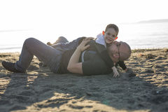 Son on father shoulders at the beach having fun  sunset together Royalty Free Stock Images
