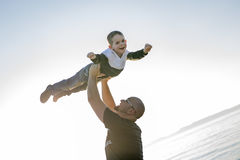 Son on father shoulders at the beach having fun  sunset together Stock Photo