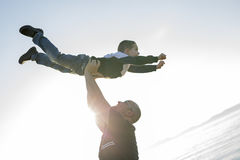 Son on father shoulders at the beach having fun  sunset together Stock Image