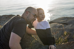 Son on father shoulders at the beach having fun  sunset together Stock Photography