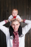 Son on father shoulders in studio. Background Stock Images
