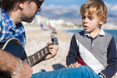 Son and father singing song on beach Royalty Free Stock Photography