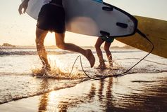 Son and father surfers run in ocean waves with long boards. Clos Royalty Free Stock Photography