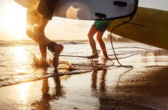 Son and father surfers run in ocean waves with long boards Royalty Free Stock Photo