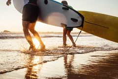 Son and father surfers run in ocean waves with surfing boards Royalty Free Stock Photography