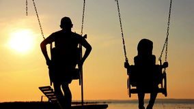 Son and father swinging on a swing at sunset, dawn, near the river, silhouettes stock footage