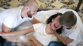 Son and father tickling mother on bed, happy family having fun time together at home