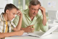 Son and father using laptop at home stock photography