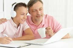 Son and father using laptop. At home stock image