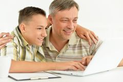Son and father using laptop. At home stock photos