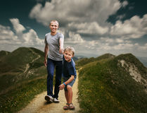 Son with father walking on the highmountain footpath royalty free stock photography