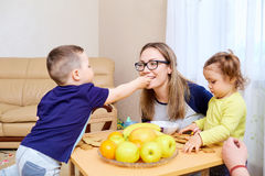 The son feeds his mother mom apple in room at table.  Stock Photography