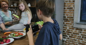 Son filming video of parents and sister cooking in kitchen on cell smart phone happy family together at home preparing stock footage