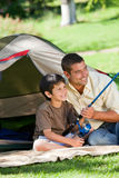 Son fishing with his father. Joyful son fishing with his father Royalty Free Stock Image