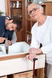 Son fixing tap. Young men fixing a tap for an old aldy stock photography