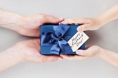 Son gives daddy present or gift box with tag on Happy fathers day. Holiday concept top view. Son gives daddy present or gift box with tag on Happy fathers day royalty free stock images