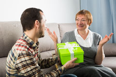 Son gives gift to mother. Son gives gift in green box for birthday to his mother at home royalty free stock photos