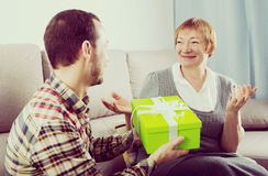 Son gives gift to mother. Son gives holiday gift box to elderly mother at home royalty free stock photos