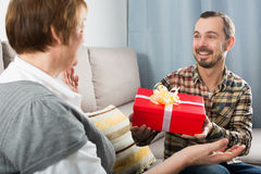 Son gives gift to mother. Son gives gift in red box to his elderly mother for birthday royalty free stock photos