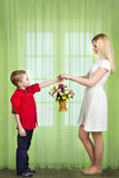 Son gives his beloved mother a basket of flowers. Spring concept of family vacation. Women`s day. Spring concept of family vacation. Women`s day royalty free stock photography