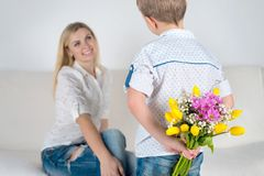 Son gives his beloved mother a beautiful bouquet of tulips.The concept of the celebration,women`s day. The concept of the celebration,women`s day.Son gives his stock images