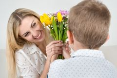 Son gives his beloved mother a beautiful bouquet of tulips.The concept of the celebration,women`s day. The concept of the celebration,women`s day.Son gives his stock photos