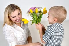 Son gives his beloved mother a beautiful bouquet of tulips.The concept of the celebration,women`s day. The concept of the celebration,women`s day.Son gives his royalty free stock images