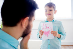Son gives his father a drawing. Boy offering a heart drawing to his father Royalty Free Stock Photography