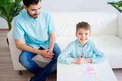 Son gives his father a drawing. Boy offering a heart drawing to his father Stock Photography