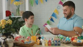 Son gives holiday easter card to dad. Family at home stock footage