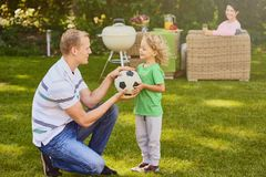 Son giving ball to father. Little sweet son giving a football ball to his father stock photo