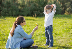 Son giving a bouquet of flowers to his pregnant mother in a fiel. Happy cute son giving a bouquet of flowers to his pregnant mother in a sunny field Stock Images