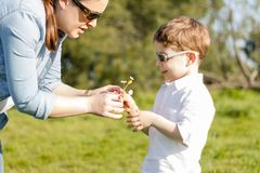 Son giving bouquet of flowers to mother in field Stock Image