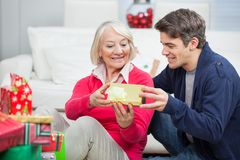 Son Giving Christmas Gift To Mother. Happy son giving Christmas gift to mother at home Stock Image