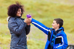Son giving flowers to his mother. Outdoor Royalty Free Stock Photo