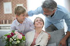 Son giving flowers to his mother on mother's day. Young boy giving flowers to mommy for mother's day Stock Photography
