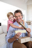 Son giving gift box to father in living room. At home Royalty Free Stock Image