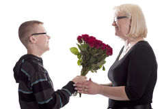 Son giving his mother a bunch of red roses Royalty Free Stock Photo