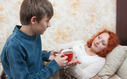 Son giving his mother tea Royalty Free Stock Photo
