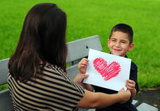 Son giving mom heart drawing. Young boy giving his mother a heart drawing for a present Stock Photography
