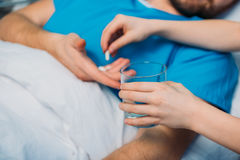Son giving pills and glass of water to his sick father laying at ward. Dad and son Royalty Free Stock Photo