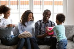 Son giving present in gift box to happy african dad. Cute little boy son gives present in gift box to happy african dad celebrating daddys birthday, black family stock photos